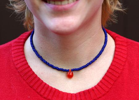Kornblått halsband med orange droppe