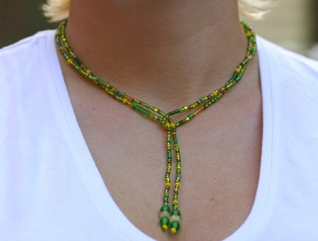 Grönt halsband bestående av en lång pärltråd att vira runt halsen