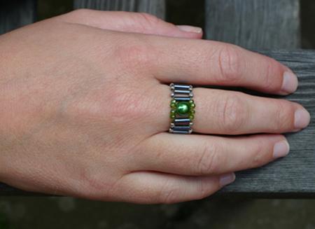 Bred ring av gröna och svarta glaspärlor, samt silvriga metallpärlor
